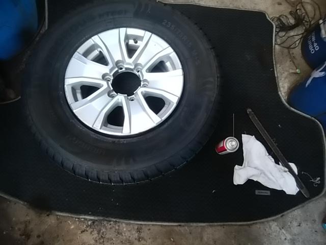 手作業でアルミホイールにタイヤを組み付ける